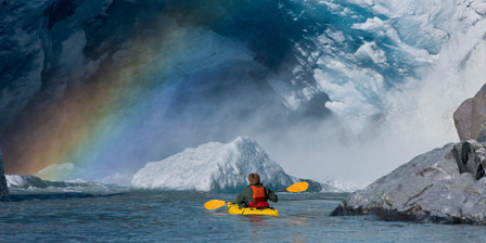 A kayaker explores a melt stream gushing from beneath Men...