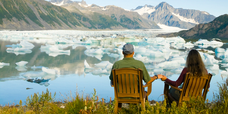 Couple relaxing along Bear Glacier Lake with Kenai Mounta...