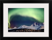Aurora Borealis over hillside neighborhood & Chugach Mountains Anchorage Alaska