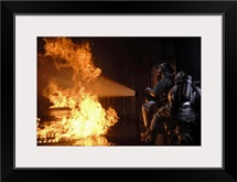 Firefighters extinguish a simulated battery fire