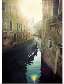 Two gondolas floating in water surrounded by old buildings.