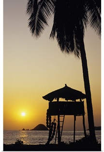 Mexico, Ixtapa Coast, Beach Bungalow And Palm Tree Silhouette At Sunset