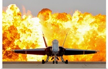 An F/A 18 Hornet sits on the flight line as a wall of fire detonates behind it