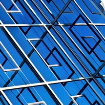 Blue, abstract and geometric reflection on  facade of modern building.