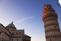 Sunlight on the top of the Leaning tower of Pisa at dusk, with the Duomo