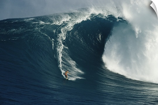A surfer rides a powerful wave off the north shore of Maui Island, Hawaii