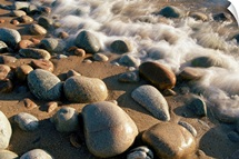 Water washes up on smooth stones lining a beach, Lake Superior, Ontario, Canada