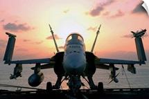 The sun rises on an F/A18 Hornet
