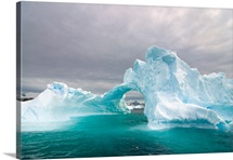 Arched iceberg floating off the Western Antarctic Peninsula, Southern Ocean, Antarctica