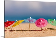 Close-Up Of Cocktail Umbrellas In The Sand