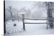 Fence with wagon wheel and trees covered in ice and snow