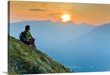Hiker sits on steep hillside of Mt. Alyeska watching the sun set