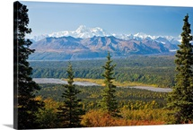 Large forest border swift river and mountain range with Mt. Mckinley in the distance