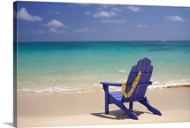 Plumeria Lei Hanging Over Blue Beach Chair Along Shoreline