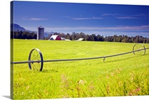 Rolling irrigation sprinkler on hay field w/farm background, Mat Su Valley, Alaska
