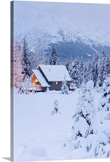 Snowcovered home in a wintry meadow at dawn with inside lights on Girdwood