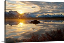 Sun rises over the Chugach Mountains with a pond and beaver lodge in the foreground