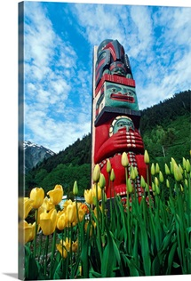 Totem pole with tulips Juneau Southeast Alaska mountains coast summer tourist
