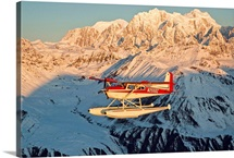 View of a Cessna 185 floatplane in Alaska Range over Ruth Glacier at sunset