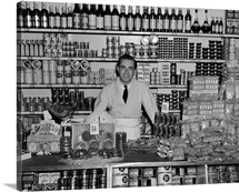 1940's Grocer Standing Behind Counter Filled With Various Food Products