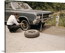1960's Man Changing Flat Tire On Car At Side Of Rural Road Car Jack Tools Tire Iron