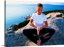 Girl meditating on rock