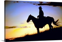 Silhouette of a cowboy on horseback at sundown.