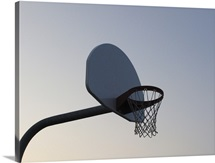 A basketball backboard hoop and net. Clear blue sky