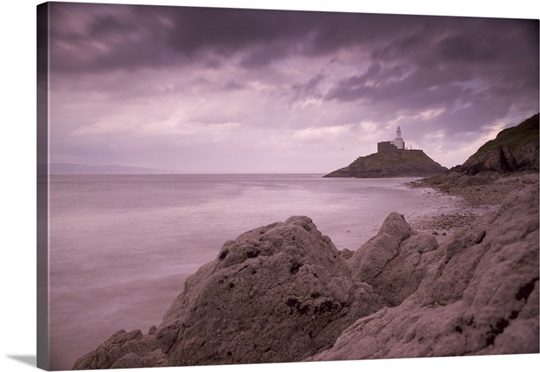 A landscape view across the shore to the lighthouse on Mumbles Head