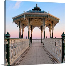 A lone figure and an almost symmetrical shot of an ornate seaside bandstand.