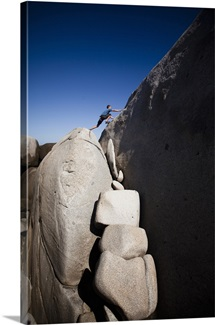 A man stretches out to explore atop giant boulders on the beach