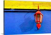 A red streetlamp on a blue and yellow wall.