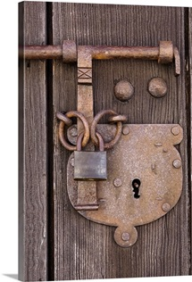 a rusted lock and keyhole on an old wooden door inside the walls of a castle