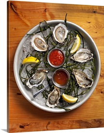 A selection of raw oysters arranged on a large platter with ice and spicy sauces