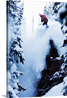 A snowboarder jumping off a cliff in the backcountry in Colorado.