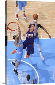 Alex Len of the Phoenix Suns shoots against Omri Casspi of the Sacramento Kings
