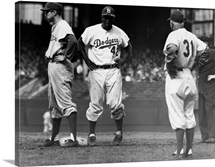 American baseball player Jackie Robinson of the Brooklyn Dodgers stands on first base