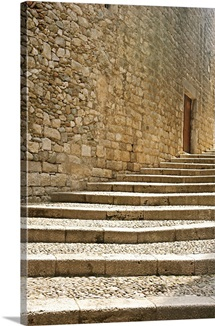 Ascending stone steps set into pale stonework of medieval walled city of Girona.