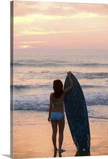 Asian girl holding surfboard at beach