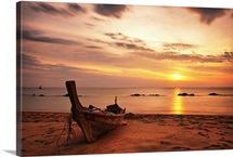 Boat on beach at sunset on Koh Lanta, Thailand.