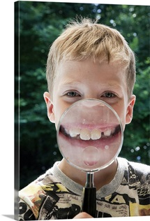 Boy behind magnifying glass smiling
