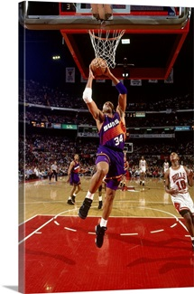 Charles Barkley of the Phoenix Suns attempts a dunk against B.J. Armstrong