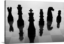 Chess pieces on chess board in black and white silhouette.