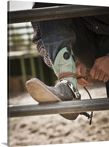 Close-up of cowboy tying shoe,  Highland, Utah