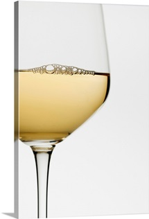 Close up of glass of white wine on white background