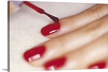 Close-up studio shot of woman applying nail polish