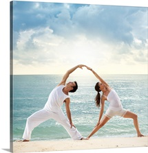 Couple Doing Yoga on a Beach