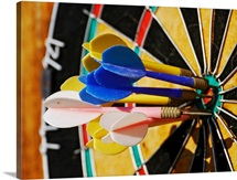 Dartboard with darts in bulls eye.