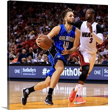 Evan Fournier of the Orlando Magic drives against Dwyane Wade of the Miami Heat