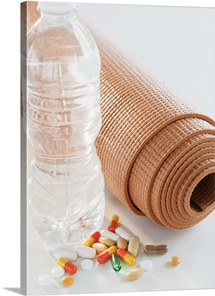 Exercise mat, water bottle and colorful pills, studio shot